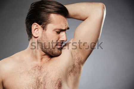 Young man shaving with electric shaver Stock photo © deandrobot