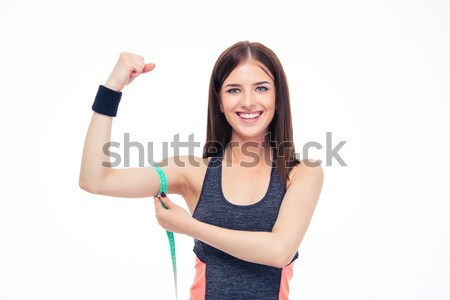 Woman measuring her biceps with measurement tape Stock photo © deandrobot