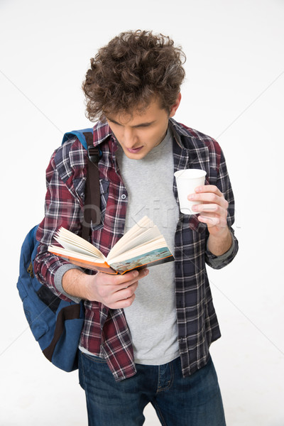 Young male student standing with book and coffee Stock photo © deandrobot