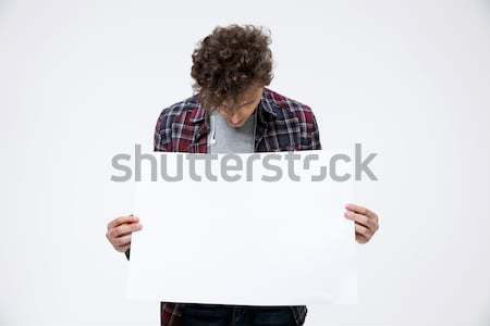 Young man holding blank billboard and looking on it Stock photo © deandrobot