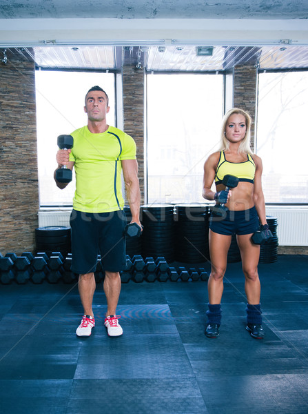 Woman and man working out with dumbbells Stock photo © deandrobot