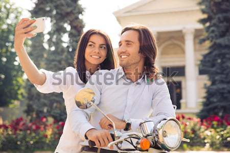 Smiling young couple on scooter together Stock photo © deandrobot
