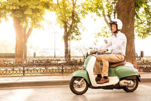 Trendy man driving a scooter in helmet. Sun is shining through trees on background Stock photo © deandrobot