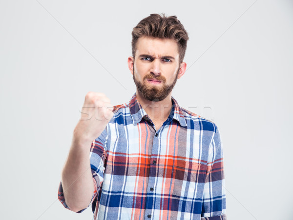 Serious man showing fist at camera  Stock photo © deandrobot