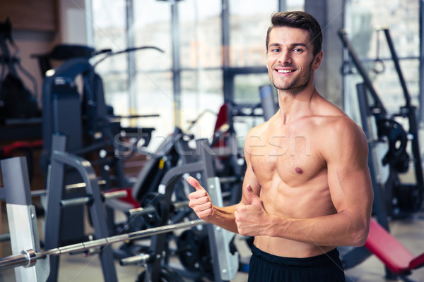 Muscular man showing thumbs up at gym Stock photo © deandrobot