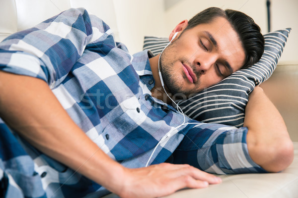 Man sleeping on the sofa with headphones at home Stock photo © deandrobot