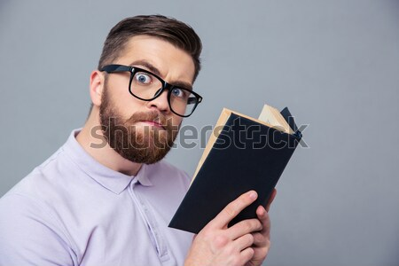Portrait of a serious casual man holding book Stock photo © deandrobot