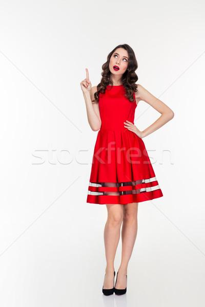 Dalgın kadın kırmızı elbise işaret parmak yukarı Stok fotoğraf © deandrobot
