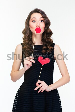 Stock photo: Beautiful alluring young woman standing and holding heart shaped lollipop