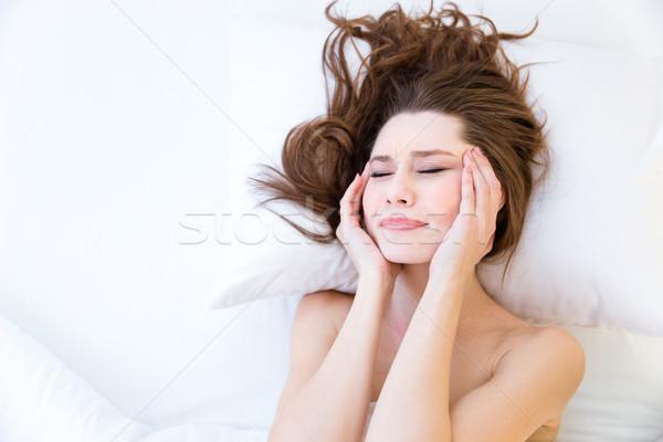Bela mulher sofrimento dor de cabeça cama belo mulher jovem Foto stock © deandrobot