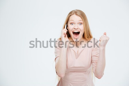 Excited woman talking on the phone Stock photo © deandrobot