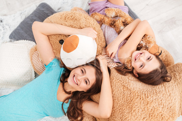 Cheerful cute sisters lying on soft plush bear at home  Stock photo © deandrobot