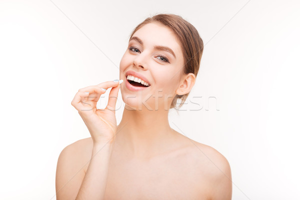 Smiling woman holding pill Stock photo © deandrobot