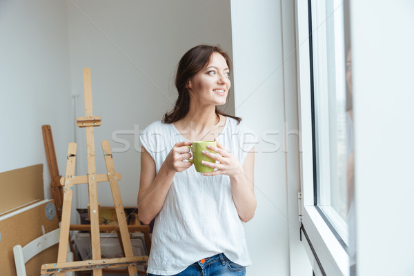 Souriant jolie femme artiste potable café atelier Photo stock © deandrobot