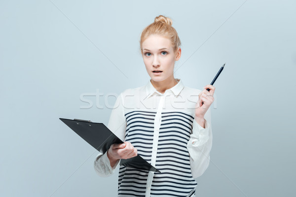 Pensive young woman holding clipboard  Stock photo © deandrobot