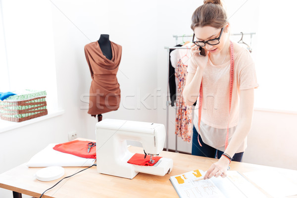 Woman seamstress working and talking on mobile phone Stock photo © deandrobot