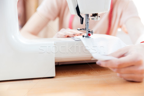 Woman seamstress sews clothes and put thread in needle Stock photo © deandrobot