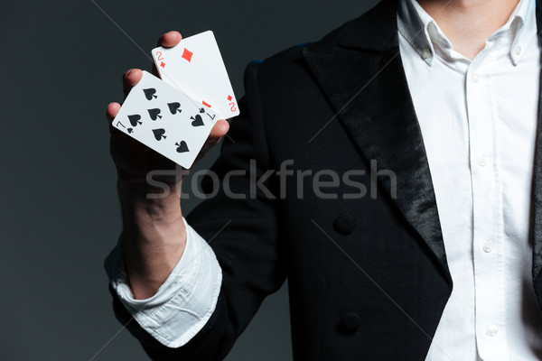 Closeup of man magician holding two playing cards Stock photo © deandrobot
