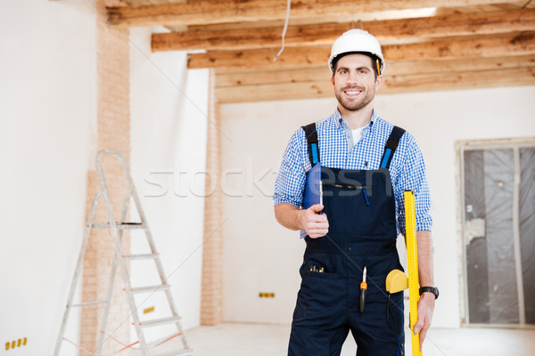 Young handsome builder standing and smiling at the working place Stock photo © deandrobot