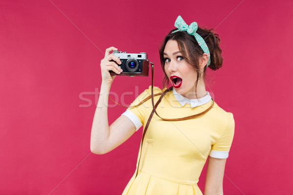 Amazed beautiful pinup girl in yellow dress holding old camera Stock photo © deandrobot
