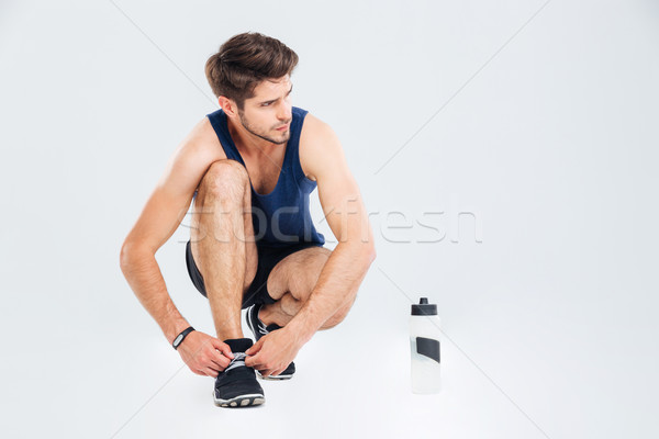 Man athlete with bottle of water tie shoelaces on sneakers Stock photo © deandrobot