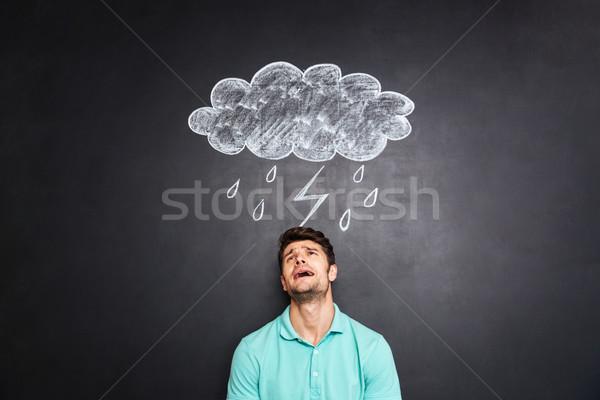 Desperate depressed man crying under rain drawn on chalkboard background Stock photo © deandrobot