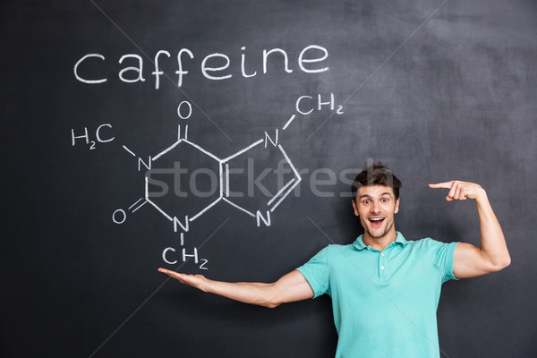 Cheerful young teacher pointing on chemical structure of caffeine molecule Stock photo © deandrobot