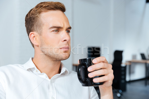 Ciddi işadamı içme kahve konsantre genç Stok fotoğraf © deandrobot