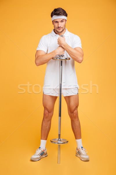 Confident attractive young sportsman standing and holding barbell Stock photo © deandrobot