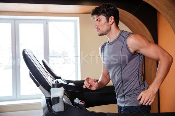 Man athlete warming up and running in treadmill in gym Stock photo © deandrobot