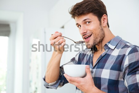 Happy young man eating cereals with milk at home Stock photo © deandrobot