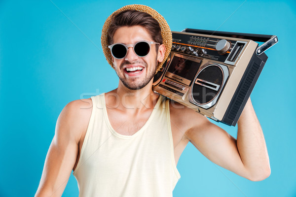 Happy young man in hat and sunglasses with boombox Stock photo © deandrobot