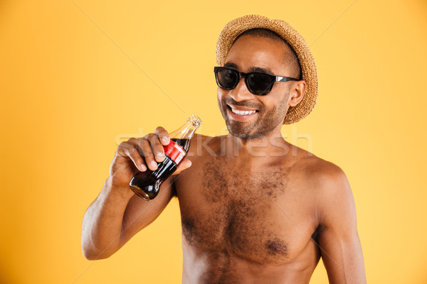 Cheerful young man in hat and sunglasses drinking coke Stock photo © deandrobot