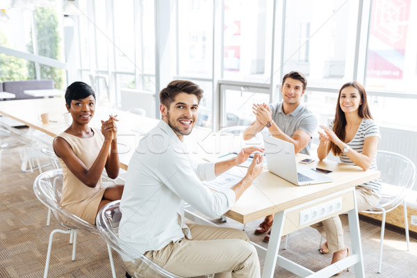 Business people sitting and clapping hands during presentation in office Stock photo © deandrobot
