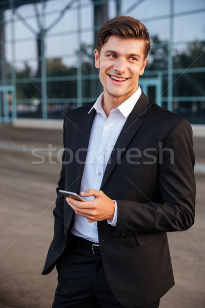 Happy young businessman with mobile phone standing outdoors Stock photo © deandrobot
