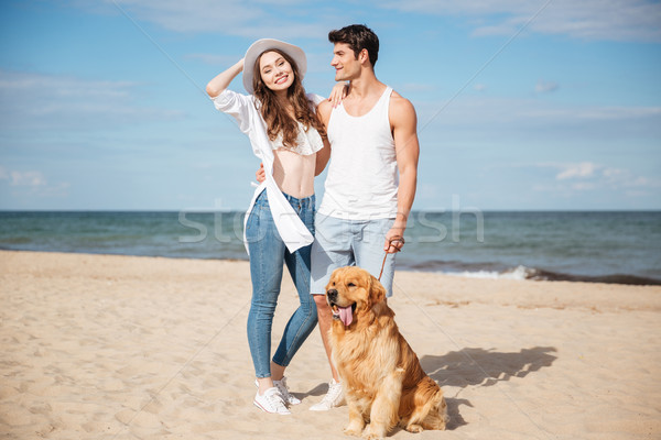 Romantic young couple standing on the sea shore with dog Stock photo © deandrobot