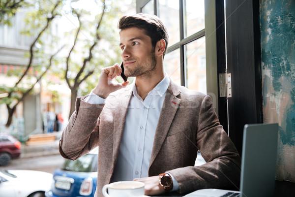 Fiatal jóképű üzletember készít telefonbeszélgetés kávézó Stock fotó © deandrobot