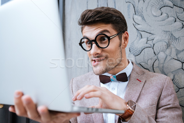Nerd man holding laptop and making funny face Stock photo © deandrobot