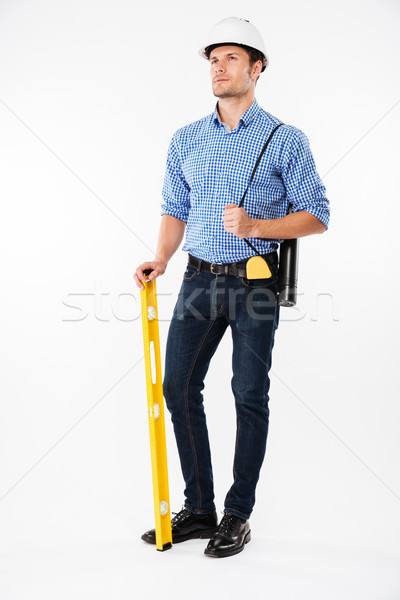 Man architect in building helmet holding spirit level and thinking Stock photo © deandrobot