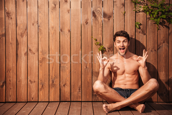 Handsome young smiling man sitting and showing okay sign Stock photo © deandrobot