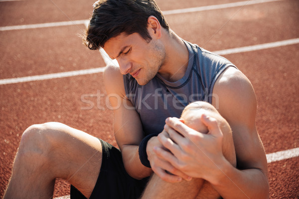 Stock photo: Close up portrait of a runner suffering from leg cramp