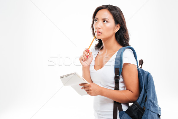 Pensive cute vietnamese teenager holding notebook annd thinking about something Stock photo © deandrobot