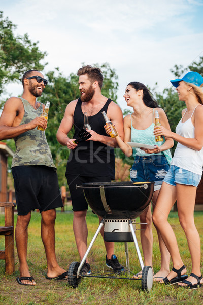 Friends drinking beer and frying meet on barbeque grill outdoors Stock photo © deandrobot
