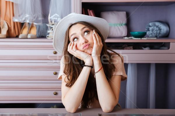 Belle jeune femme pense quelque chose placard jeunes Photo stock © deandrobot