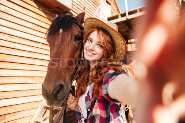Cheerful woman cowgirl standing taking selfie with horse on farm Stock photo © deandrobot
