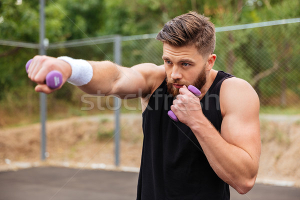Young bearded sports man doing workout with small dumbbells Stock photo © deandrobot