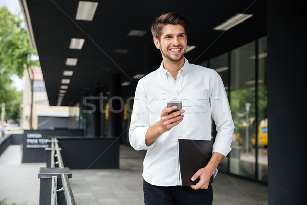 Businessman with smartphone and documents walking outdoors Stock photo © deandrobot