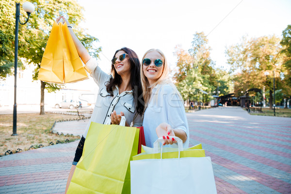 Two beautiful women with shopping bags walking in the ctiy Stock photo © deandrobot