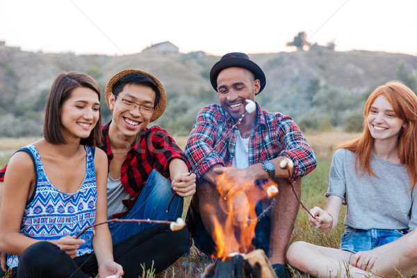 Happy young people sitting and roasting marshmallows on campfire outdoors Stock photo © deandrobot