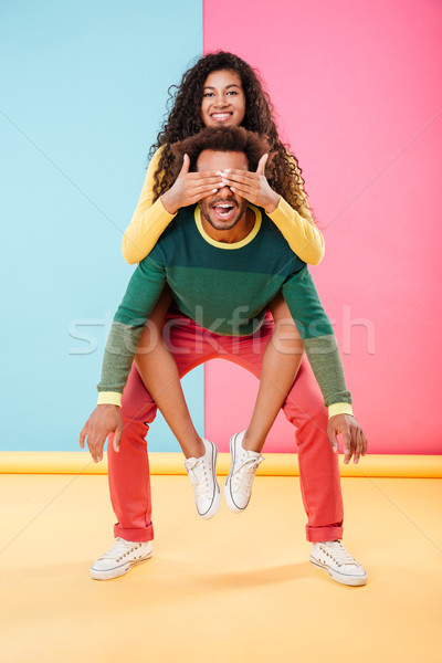 African american young man holding girlfriend on his back Stock photo © deandrobot